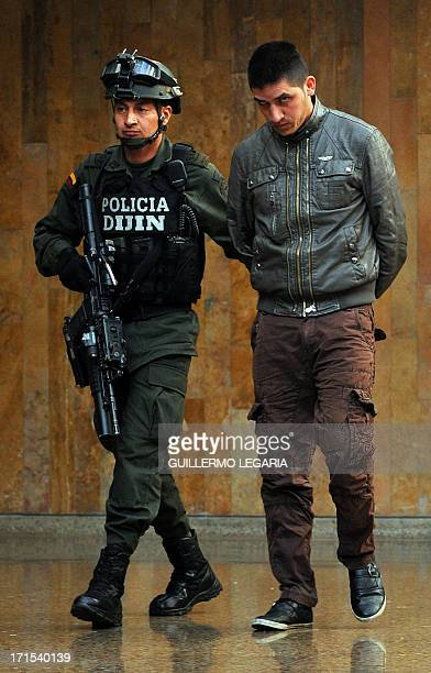 A Colombian Police officer escorts Edgar Bello Murillo alias Payaso one of four suspects in the killing of US Drug Enforcement Agency agent James...