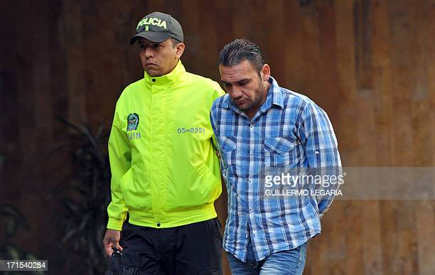 A Colombian Police officer escorts Edwin Figueroa alias Garcho one of four suspects in the killing of US Drug Enforcement Agency agent James 'Terry'...