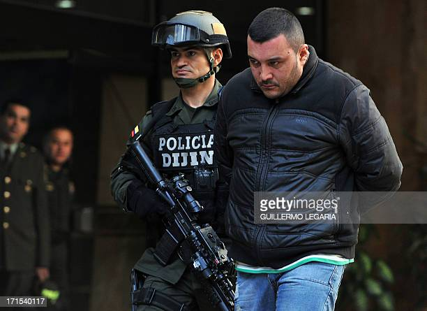 A Colombian Police officer escorts Leonardo Lopez alias Bavario one of four suspects in the killing of US Drug Enforcement Agency agent James 'Terry'...