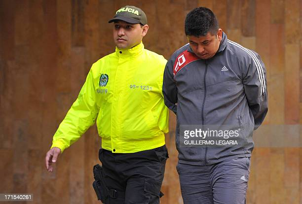 A Colombian Police officer escorts Omario Fabio Valdez alias Fabian one of four suspects in the killing of US Drug Enforcement Agency agent James...