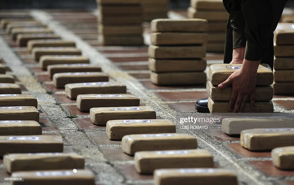 A Colombian police officer picks up packages of cocaine during a press conference in Cali department of Valle del Cauca Colombia on January 30 2014...