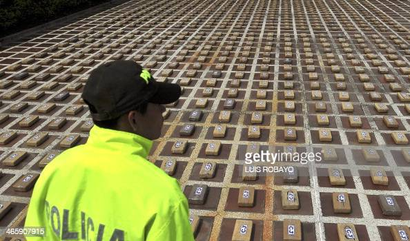 A Colombian police officer stands guard next to packages of cocaine during a press conference in Cali department of Valle del Cauca Colombia on...