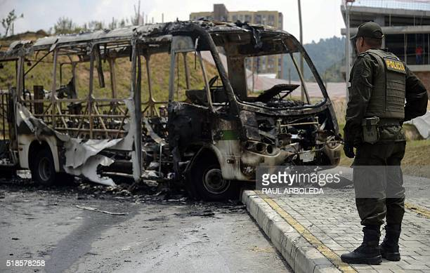 A Colombian police officer stands next to a Metro bus burned by criminal gang members in Belen neighborhood Medellin Antioquia department Colombia on...