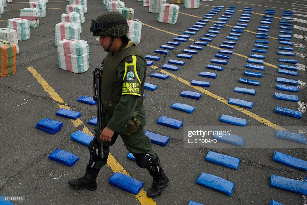 A Colombian police officer walks next to seized marijuana packages to be shown to the press, on July 21, 2013, in Cali, department of Valle del Cauca, Colombia. The National Police confiscated 5.6 tons of marijuana during a raid near the municipality of Villarica, Cauca department. According to authorities, the seized marijuana would come from an alliance between drug traffickers and the FARC guerrilas. AFP PHOTO/Luis ROBAYO