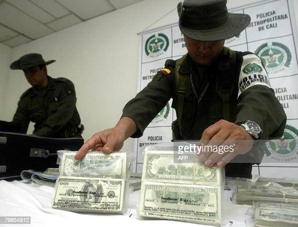 Colombian police officers arrange packages of US dollars during a press conference at Bonilla Aragon airport in Cali on February 8 2008 after the...