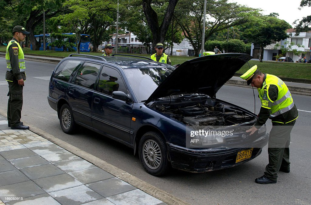 Colombian police officers check a car at a checkpoint in Cali, Valle del Cauca departament, Colombia, on May 22, 2013, as part of security measure for the next VII Pacific Alliance presidential summit to be held on May 23. AFP PHOTO/Luis ROBAYO