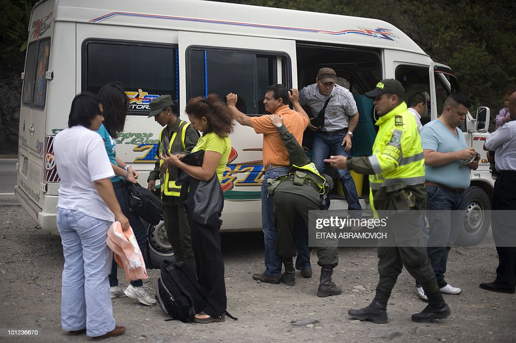 Colombian police officers frisk passengers of a small bus at a checkpoint in El Tablon, Cundinamarca department, on May 28, 2010. Colombia will hold presidential elections next May 30, and according to polls, a run-off election between Antanas Mockus for the Green Party and Juan Manuel Santos for the ruling National Unity Party, will take place on June 20. AFP PHOTO/Eitan Abramovich