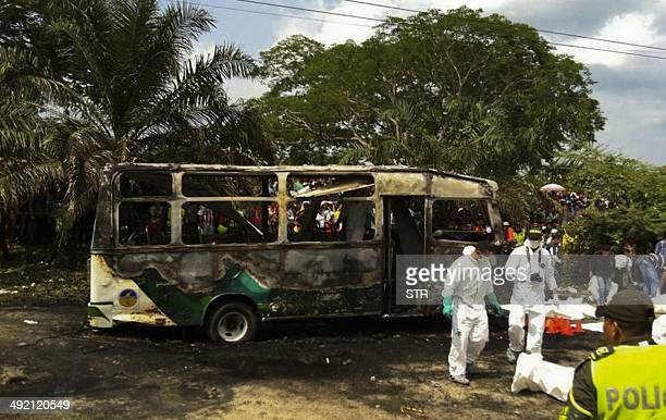 Colombian police stand alongside recovered bodies of children who died in a burned bus in Fundacion Colombia on May 18 2014 Thirtyone children were...