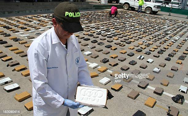 Colombian policemen from an antidrug unit opens a package of cocaine part of a seizure of 1825 kg worth USD 3 million during a press conference in...