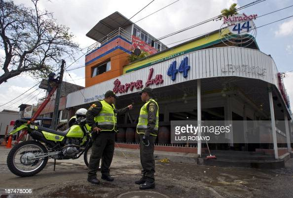 Colombian policemen stand outside 'Barra la 44' disco bar on November 9 2013 in Cali department of Valle del Cauca Colombia where a shooting on the...