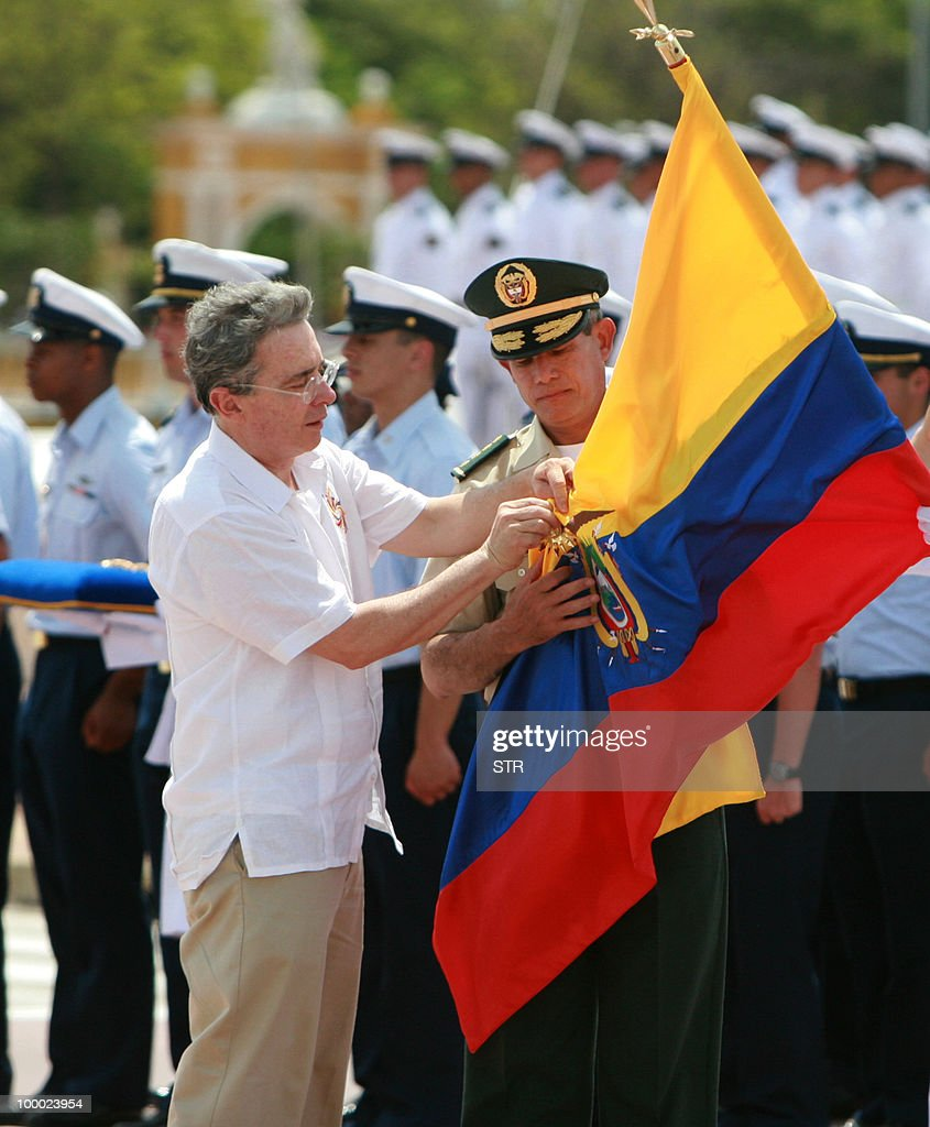 Colombian President Alvaro Uribe pins a decoration on an Ecuadorean flag during ca eremony in front of Ecuadorean sailboat Guayas upon her arrival at the port of Cartagena, Colombia during the Bicentennial Race, on May 20, 2010. Eleven training ships from America and Europe are taking part in the international regatta to commemorate the independence bicentennial of several Latin American countries.