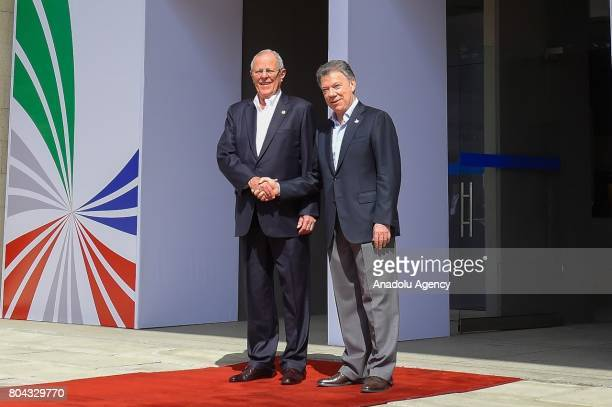 Colombian President Juan Manuel Santos and Peruvian President Pedro Pablo Kuczynski shake hands as they pose for a photo during the welcoming...