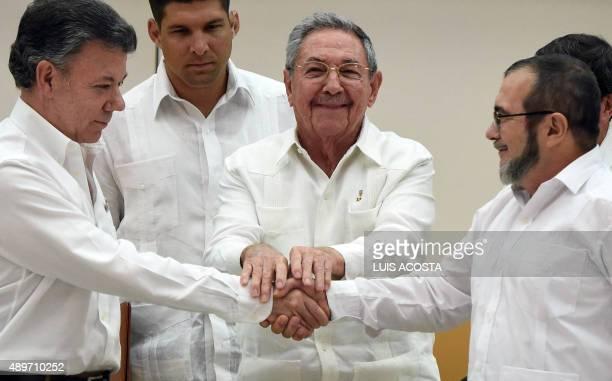 Colombian President Juan Manuel Santos and the head of the FARC guerrilla Timoleon Jimenez aka Timochenko shake hands as Cuban President Raul Castro...