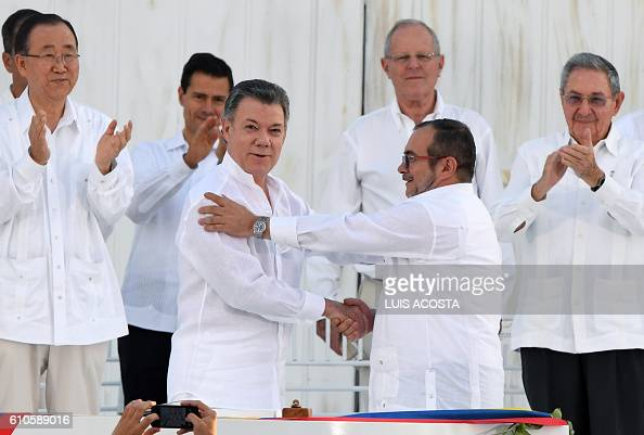 TOPSHOT Colombian President Juan Manuel Santos and the head of the FARC guerrilla Timoleon Jimenez aka Timochenko shake hands during the signing of...