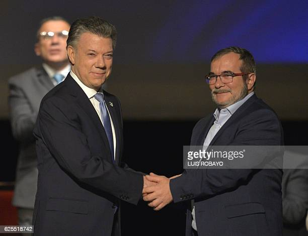 Colombian President Juan Manuel Santos and the head of the FARC guerrilla Timoleon Jimenez aka Timochenko shake hands during the second signing of...