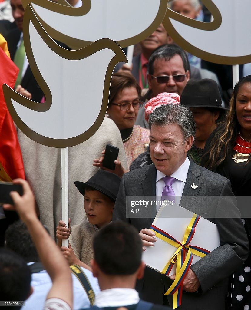 Colombian President Juan Manuel Santos carries a copy with the final text of the peace agreement with the Revolutionary Armed Forces of Colombia...