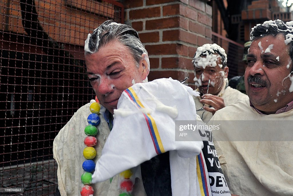 Colombian President Juan Manuel Santos (L) cleans foam off his face during the 'White Day' parade, part of the Carnival of Blacks and Whites in Pasto, Colombia, on January, 6, 2013. The Carnival of Blacks and Whites was declared by UNESCO as 'Intangible Cultural Heritage of Humanity', and is celebrated every year on the eve of the 'Three Kings Day'. AFP PHOTO/Luis ROBAYO