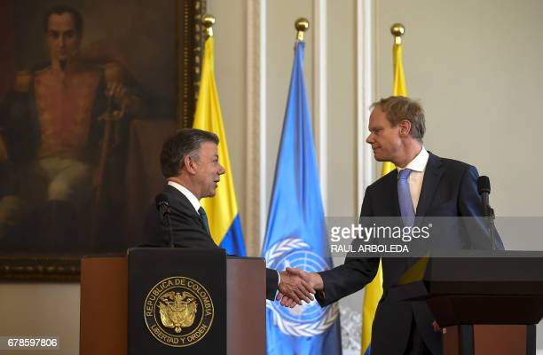 Colombian President Juan Manuel Santos shakes hands with Great Britain's Ambassador at the United Nations Matthew Rycroft during a meeting at Narino...