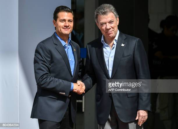 Colombian President Juan Manuel Santos shakes hands with his Mexican counterpart Enrique Pena Nieto during the welcoming ceremony of the XII Pacific...