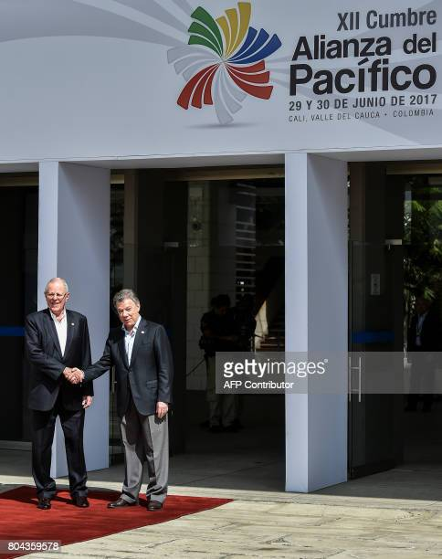 Colombian President Juan Manuel Santos shakes hands with his Peruvian counterpart Pedro Pablo Kuczynski during the welcoming ceremony of the XII...