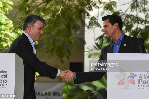 Colombian President Juan Manuel Santos shakes hands with Mexican President Enrique Pena Nieto during the final declaration of the XII Pacific...