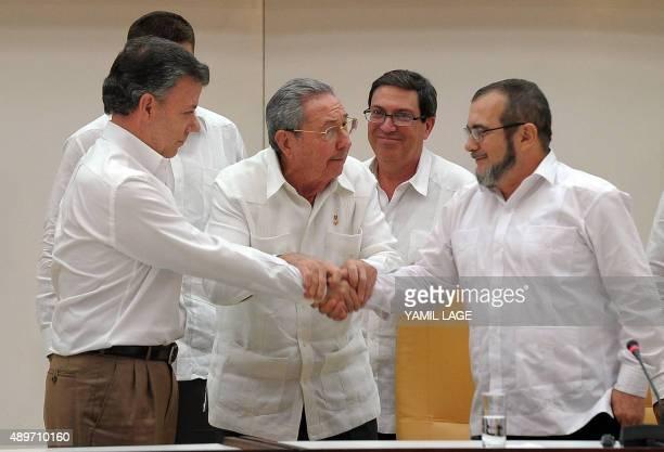Colombian President Juan Manuel Santos shakes hands with the head of the FARC guerrilla Timoleon Jimenez aka Timochenko as Cuban President Raul...
