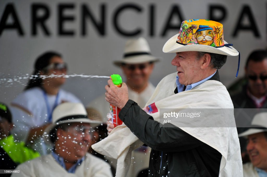 Colombian President Juan Manuel Santos takes part in the 'White Day' parade, part of the Carnival of Blacks and Whites in Pasto, Colombia, on January, 6, 2013. The Carnival of Blacks and Whites was declared by UNESCO as 'Intangible Cultural Heritage of Humanity', and is celebrated every year on the eve of the 'Three Kings Day'. AFP PHOTO/Luis ROBAYO