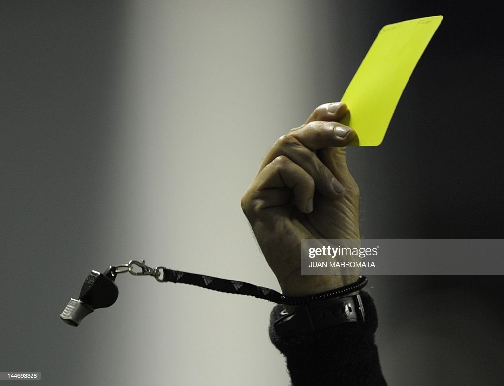Colombian referee Jose Buitrago shows the yellow card to Brazil's Fluminense defender Carlinhos during their Copa Libertadores 2012 quarterfinals...