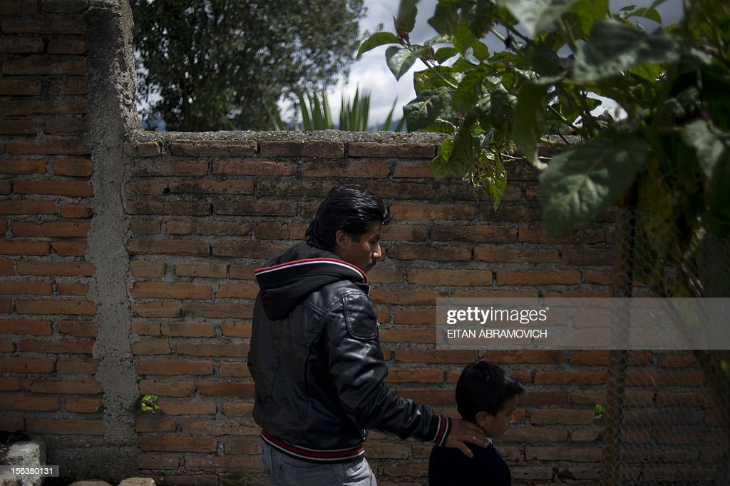 Colombian refugee walks with his Ecuadorean son at a rural school at Chitan de Navarrete, Carchi province, Ecuador, close to the border with Colombia on November 7, 2012. AFP PHOTO/Eitan Abramovich --- COLOMBIA OUT