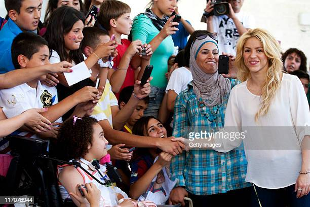 Colombian singer and UNICEF Goodwill ambassador Shakira poses with Israeli and Palestinian school children during her visit to a Bilingual school on...
