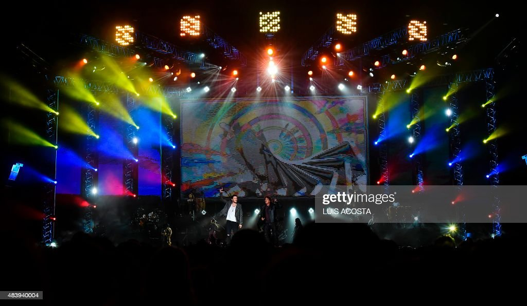 Colombian singer Carlos Vives (R) and Gusi perform during the Concert Vives and Friends at the el Campin stadium in Bogota on August 13, 2015. AFP PHOTO / Luis Acosta /