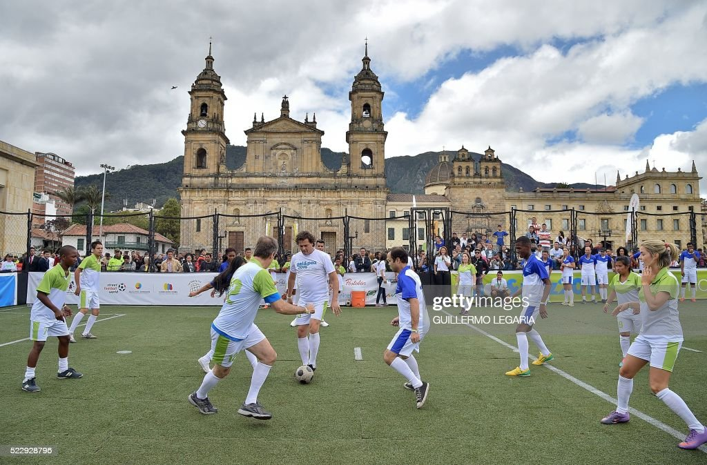 Colombian singer Carlos Vives (C) plays football at the main square in Bogota, Colombia, on April 21, 2016, during an event to promote peace, reconcilitation and social inclusion. /