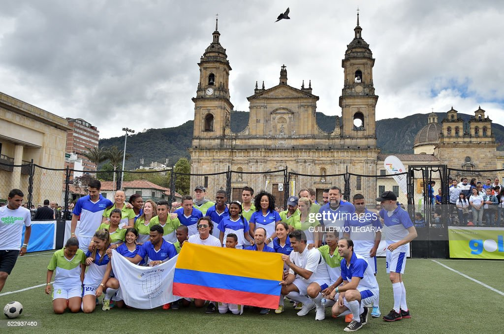 Colombian singer Carlos Vives (C) poses with celebrities and youngsters during a football event to promote peace, reconcilitation and social inclusion at the main square in Bogota, Colombia, on April 21, 2016. /