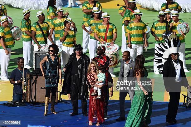 Colombian singer Shakira poses holding her son Milan alongside HaitianUS musician Wyclef Jean Brazilian singer Alexandre Pires and Mexican musician...