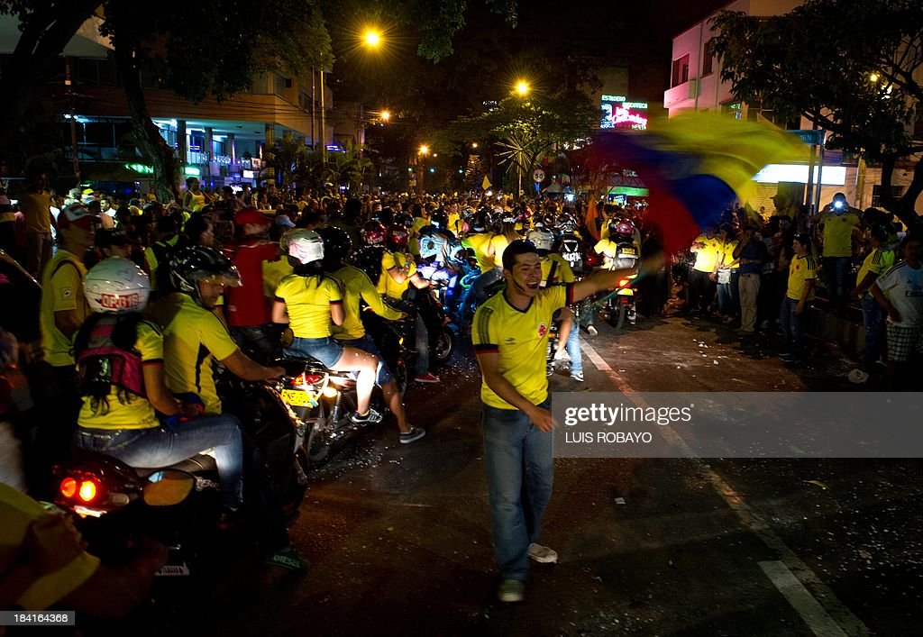 Colombian soccer fans celebrate the victory over Chile during the Brazil 2014 FIFA World Cup South American qualifier match, in Cali, Colombia, on October 11, 2013. Colombia was classified to the World Cup after 16 years. AFP PHOTO / LUIS ROBAYO