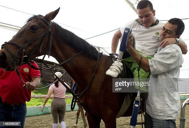Colombian soldier Deiber Arredondo victim of a landmine is helped to get down from a horse during a horse therapy rehabilitation session supported by...