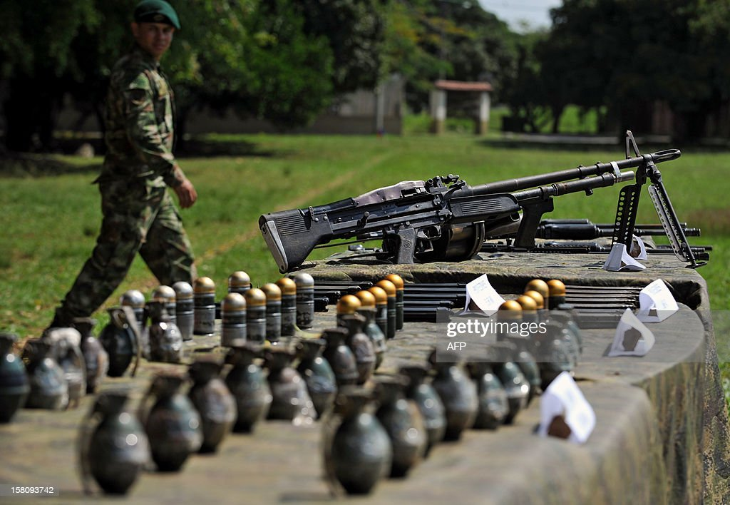 A Colombian soldier walks next to seized weapons, on December 10, 2012, in Cali, Valle del Cauca department, Colombia. Colombia's army found a cove that contained twelve 5.56mm caliber rifle, a 7.62mm machine gun, a grenade launcher, 66 kilograms of explosives, 40 grenades, and some 3000 cartridges, allegedly belonging to the Revolutionary Armed Forces of Colombia (FARC) guerrillas. AFP PHOTO / Luis ROBAYO