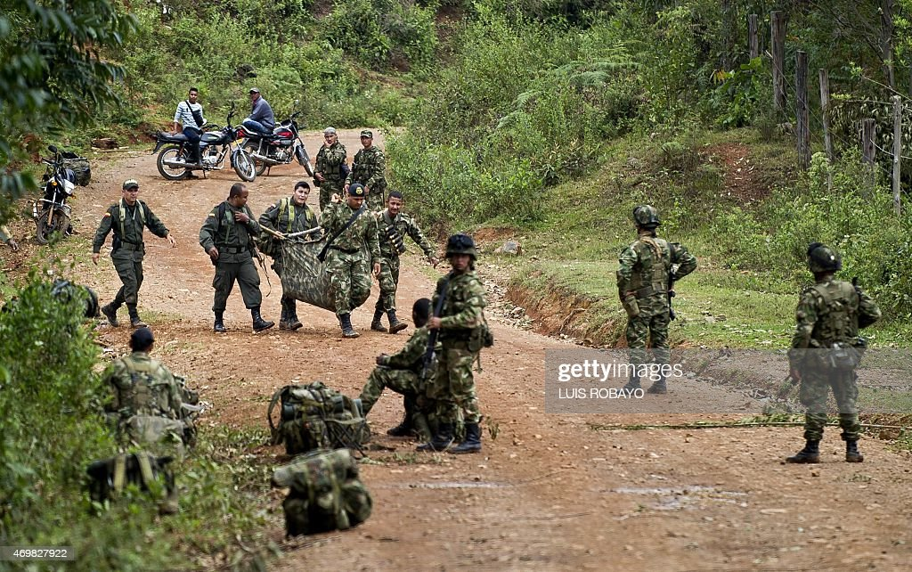Colombian soldiers carry equipment of one of ten soldiers killed by the Revolutionary Armed Forces of Colombia guerrillas in the rural area of Buenos...