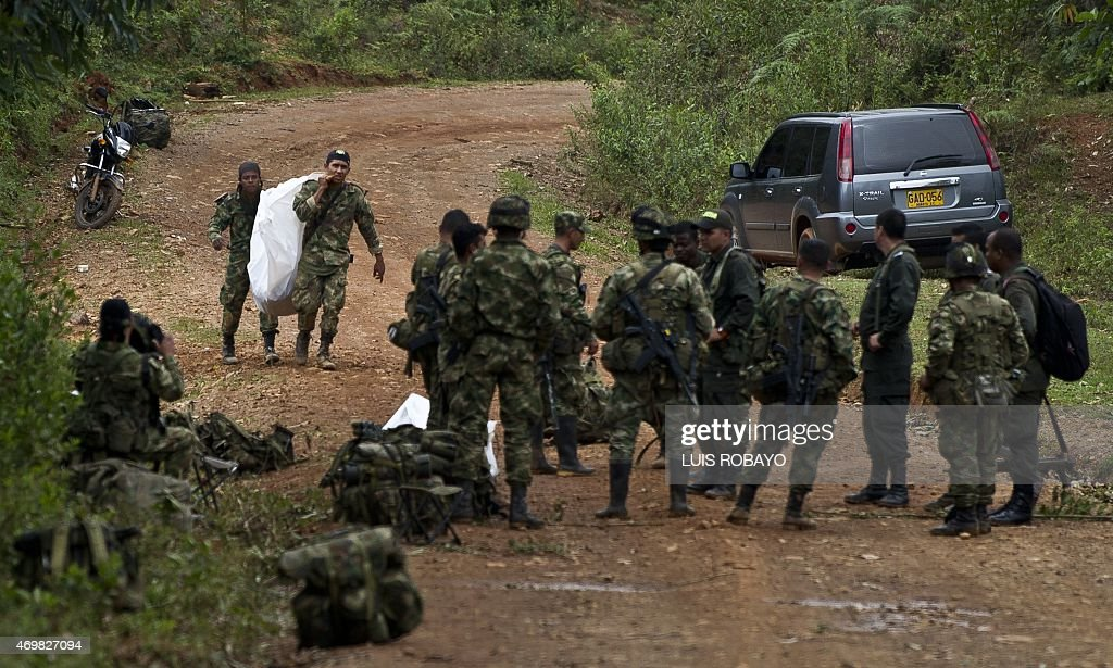 Colombian soldiers carry the corpse of one of ten soldiers killed by the Revolutionary Armed Forces of Colombia guerrillas in the rural area of...