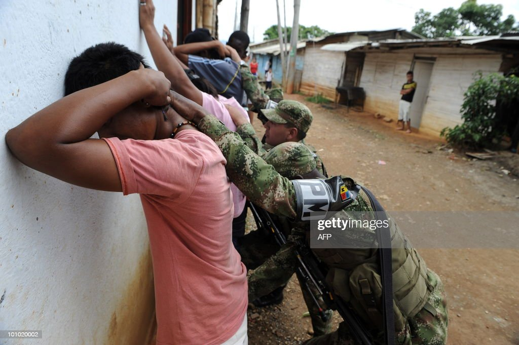 Colombian soldiers frisk a group of young people of a neighborhood on the outskirts of Cali, Valle del Cauca departament, Colombia, on May 27, 2010. Colombia will hold presidential elections next May 30. AFP PHOTO/Luis ROBAYO