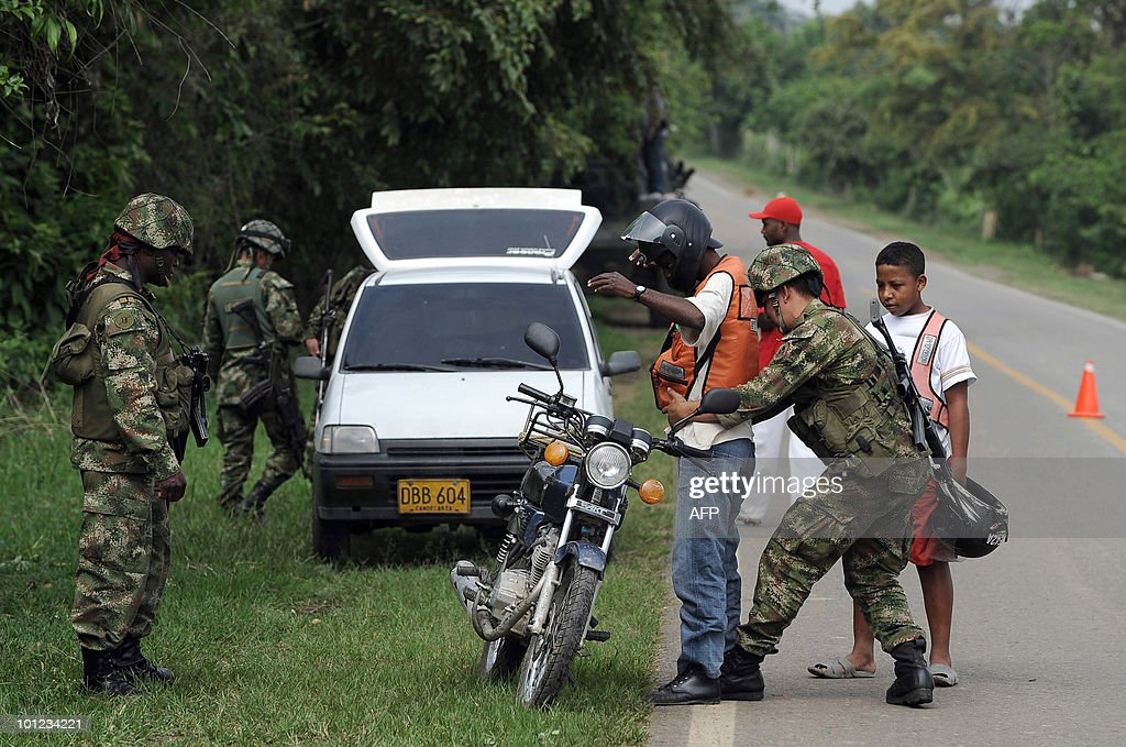 Colombian soldiers frisk a motocyclist along the Pan American Highway on May 28, 2010, in Corinto, departament of Cauca, Colombia. Colombia will hold the presidential elections next May 30. AFP PHOTO/Luis ROBAYO