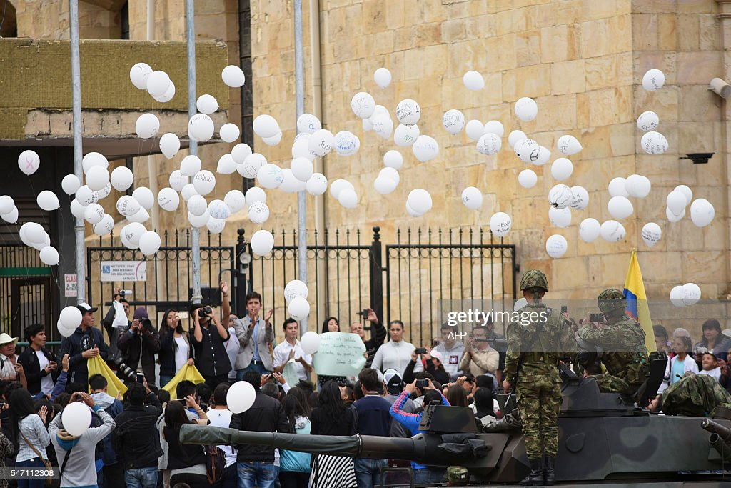 Colombian soldiers stand guard as students release white balloons at the Liberators square of Duitama in the Boyaca department on July 13 in tribute...