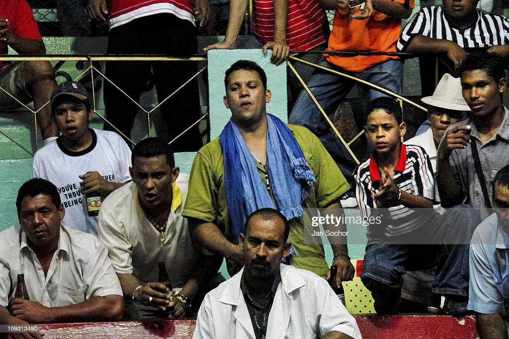 Colombian spectators watch a cockfight in the arena in Santa Marta, Colombia on May 20, 2006. Cockfight is a widely popular and legal sporting event in much of Latin America. The fight is usually held in an arena (gallera in spanish) with seats for spectators. There is always gambling involved in cockfights. People take advantage of cock's natural, strong will to fight against all males of the same species. Birds are specially bred to increase their aggression and stamina, they are given the best of food and care. The cocks are equipped with tortoise-shell made gaffs tied to the bird's leg. The fight is not intentionally to the death but it may result in the death of cocks very often.