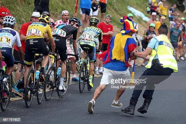 Colombian supporter is removed from the course by a Gendarmerie as the group of the yellow jersey with Nairo Quintana of Colombia riding for Movistar...