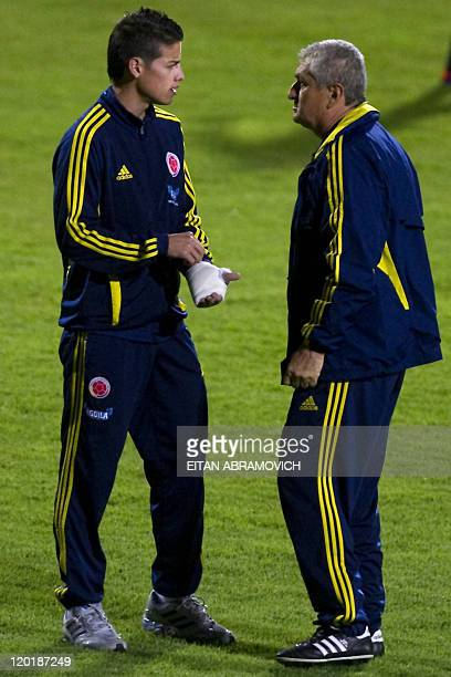 Colombian U20 national football team player James Rodriguez speaks with coach Eduardo Lara during a training session in Bogota Colombia on July 31...
