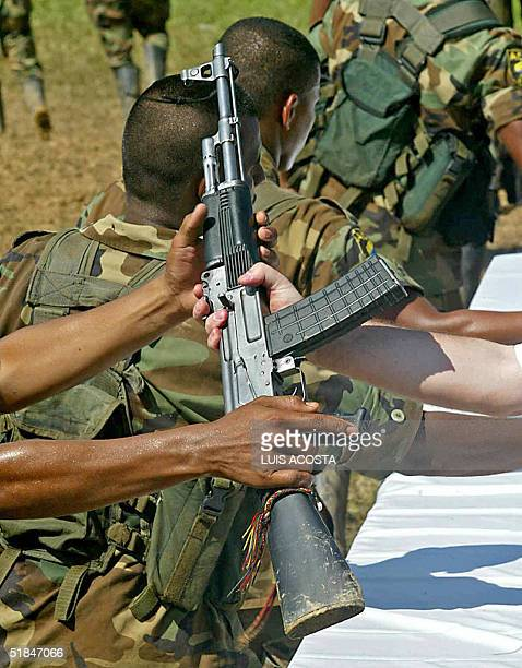Colombian United Self Defense rightwing paramilitary guerrilla fighter surrenders his assault rifle to Peace Commissioner Luis Carlos Restrepo 10...