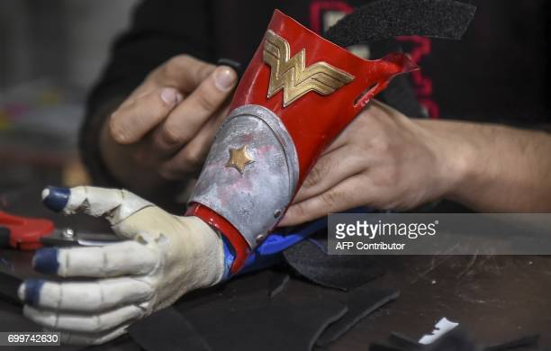 Colombian Wilmer Garcia works in a 3D printed prosthesis with superhero 'Wonder Woman' design in Bogota Colombia on June 12 2017 Fabrilab is a...