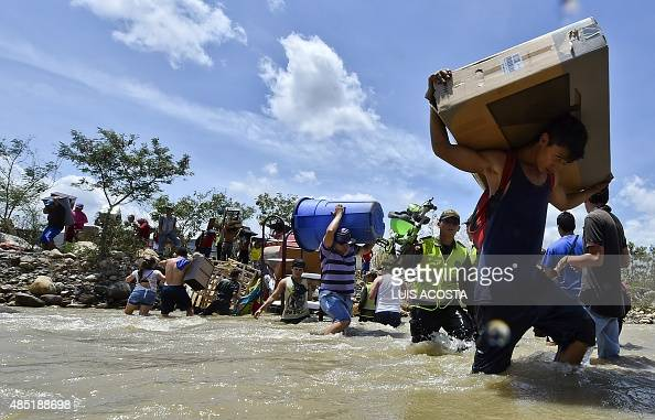 Colombians deported from Venezuela return for their belongings and carry them across the Tachira River border between the two countries to Cucuta in...