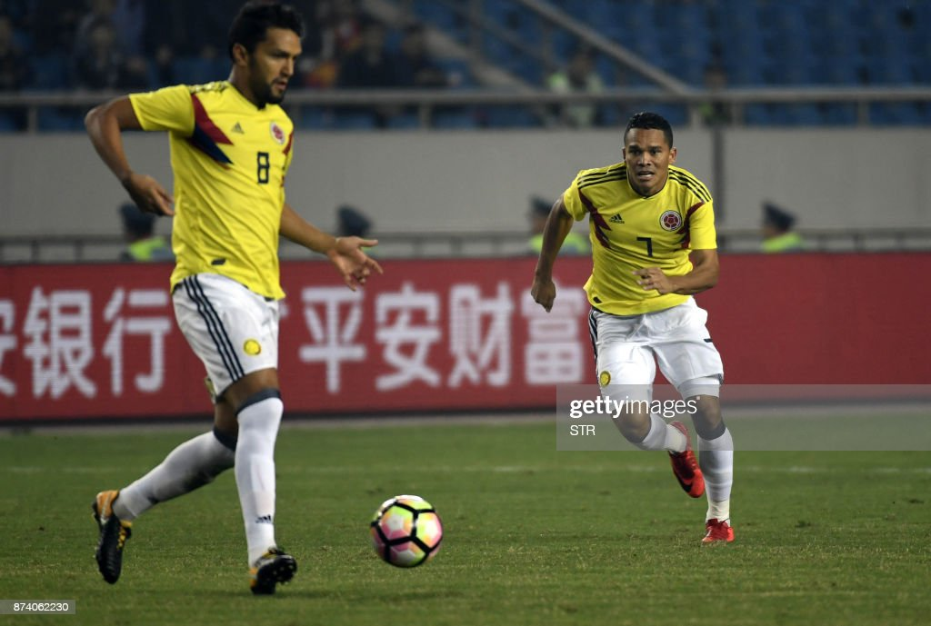 Colombia's Abel Aguilar (L) runs with the ball next to teammate Carlos Bacca during their international friendly football match against China in Chongqing, southwest China on November 14, 2017. A Colombia side missing James Rodriguez punished China 4-0 away in a friendly on November 14 as coach Jose Pekerman made wholesale changes from the team defeated in acrimony in South Korea. / AFP PHOTO / STR / China OUT