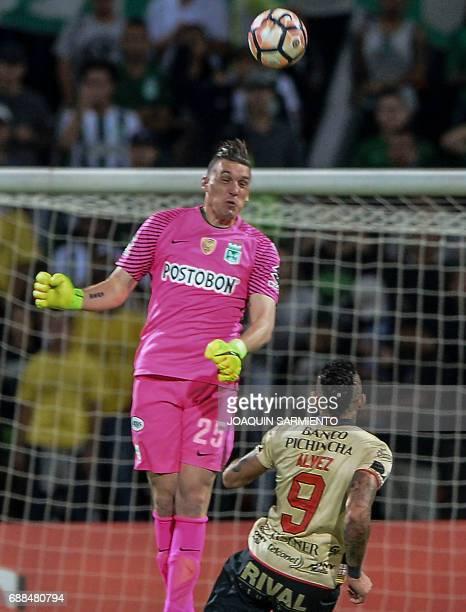 Colombia's Atletico Nacional goalkeeper Franco Armani vies for the ball with Ecuador's Barcelona player Jonathan Alvez during their Copa Libertadores...